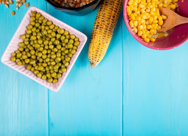 Top view of bowl of green peas with corn cob and corn seeds in bowl on blue surface with copy space