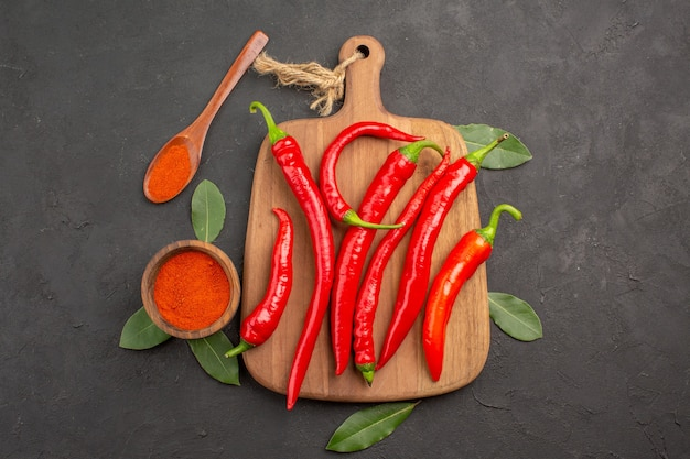 Top view a bowl of hot pepper powder red peppers on the chopping board bay leaves and a wooden spoon on the black table