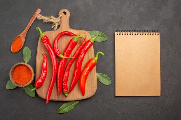Vista dall'alto una ciotola di peperoncino in polvere peperoni rossi sul tagliere foglie di alloro un cucchiaio di legno e un taccuino sulla tavola nera