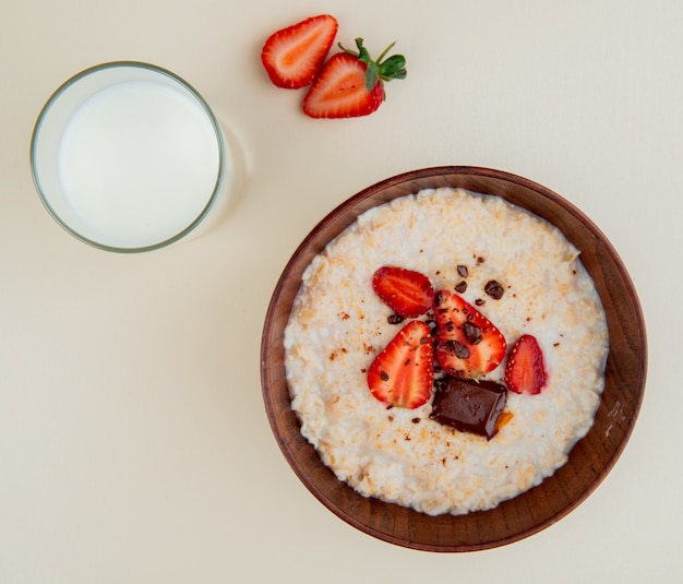 Top view of bowl of oatmeal with cottage cheese chocolate and strawberries with glass of milk on white surface