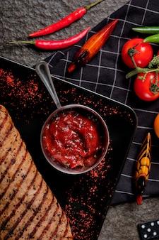 Шар взгляд сверху соуса chili, томата и чеснока на черном камне.