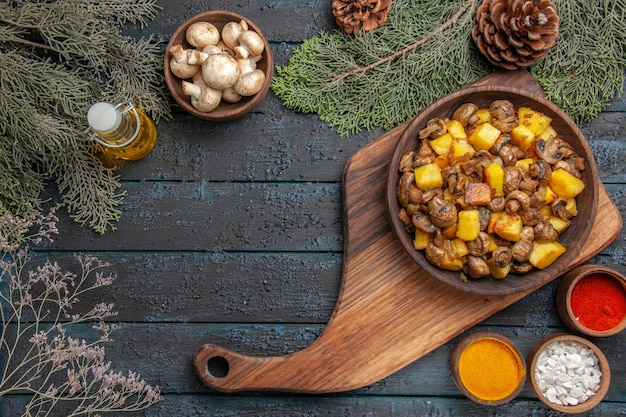 白いキノコのトウヒの枝とカラフルなスパイスのオイルボウルのボトルの間のまな板上のキノコとジャガイモのフードボウルの上面図ボウル