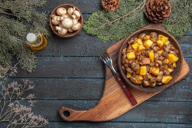 白いキノコとトウヒの枝のオイルボウルのボトルの下のフォークの横にあるまな板の上のキノコとジャガイモのフードボウルの上面図ボウル