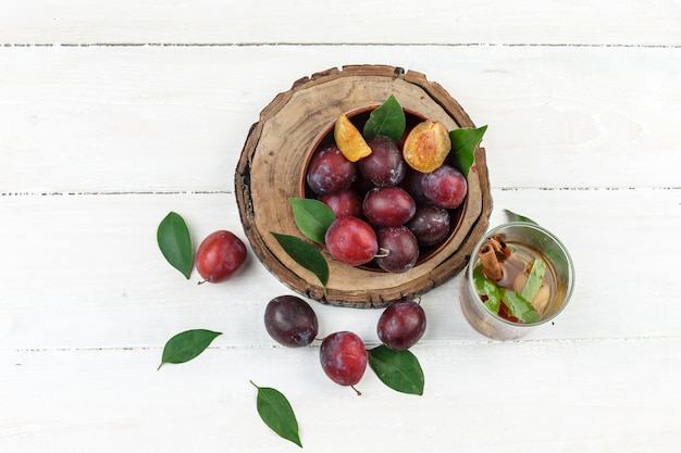 Top view a bowl of plums on wooden board with detox water and leaves on white wooden board table. horizontal