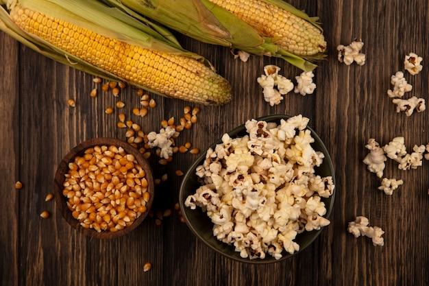 Vista dall'alto di una ciotola di popcorn con chicchi di mais su una ciotola di legno con mais fresco isolato su una parete in legno