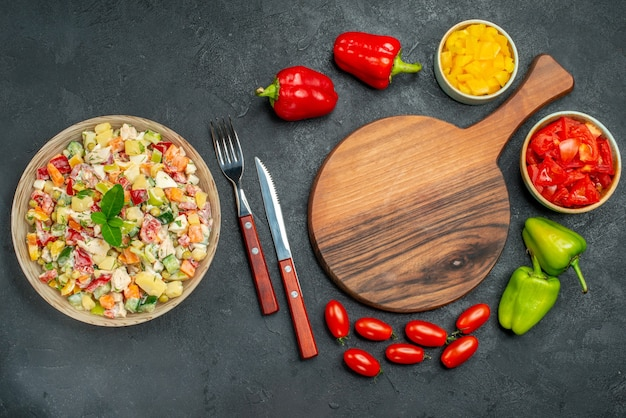 Top view of bowl of salad with plate stand cutleries veggies on dark grey background