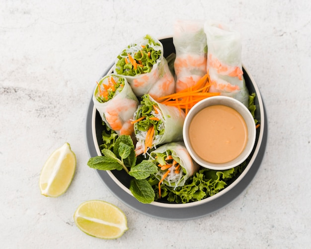 Top view of bowl of shrimp rolls with sauce and lemon