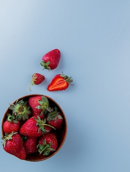 Top view of bowl of strawberries on blue surface with copy space