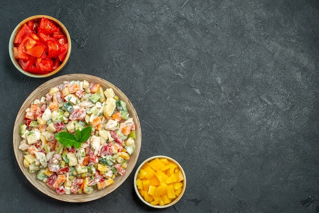 Top view of bowl of vegetable salad on left bottom side with bowls of vegetables on side on dark green-grey background