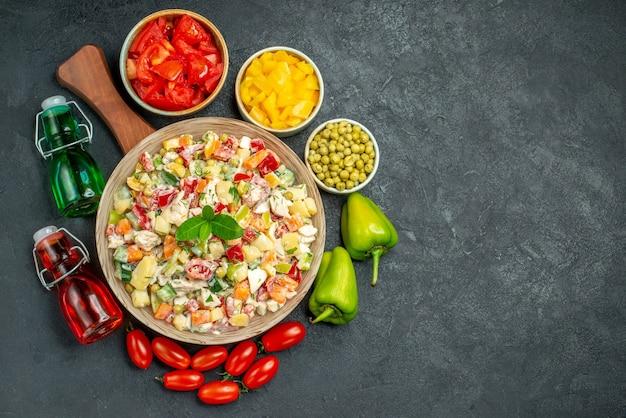 Vista dall'alto della ciotola di insalata di verdure sul supporto della piastra con verdure e bottiglie di olio e aceto sul lato e posto per il testo su sfondo grigio scuro
