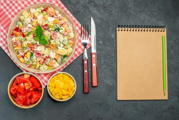 Vista dall'alto della ciotola di insalata di verdure sul tovagliolo rosso con posate di verdure e blocco note sul lato sul tavolo scuro