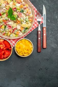 Vista dall'alto della ciotola di insalata di verdure sul tovagliolo rosso con verdure e posate sul lato e con posto libero per il testo nella parte inferiore sul tavolo scuro