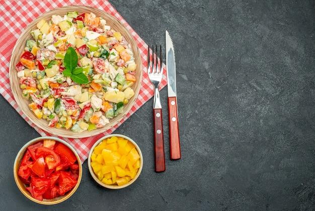 Vista dall'alto della ciotola di insalata di verdure sul tovagliolo rosso con verdure e posate sul lato e con posto libero per il testo sul tavolo scuro