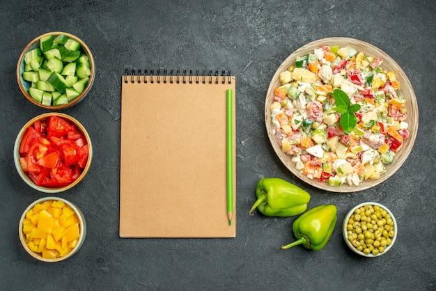 Vista dall'alto della ciotola di insalata di verdure con ciotole di blocco note di verdure e peperoni sul lato sul tavolo verde scuro Foto Gratuite