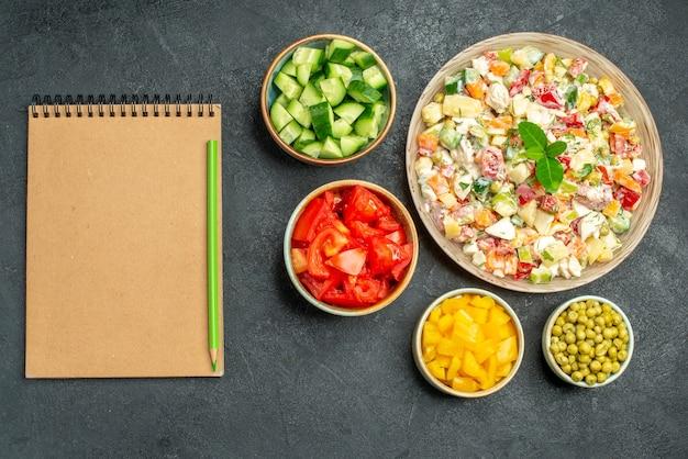 Vista dall'alto della ciotola di insalata di verdure con ciotole di verdure e blocco note con la penna su di esso sul lato su sfondo verde scuro