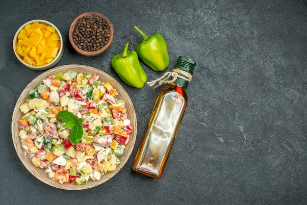 Top view of bowl of vegetable salad with bowls of vegetables and pepper oil bottle and bell peppers on side on dark background