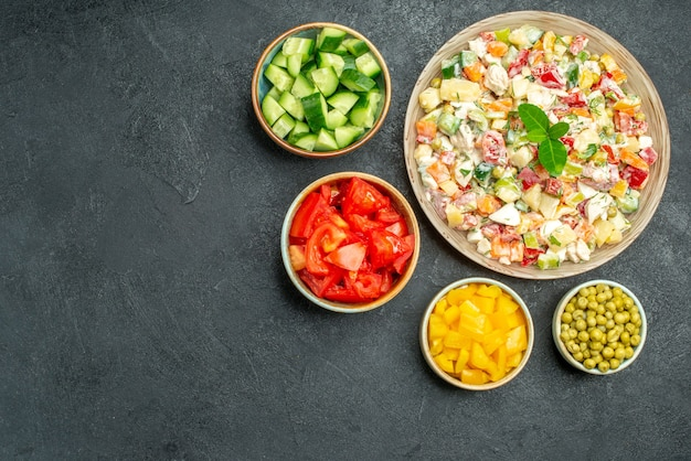 Top view of bowl of vegetable salad with bowls of vegetables on side on dark green background