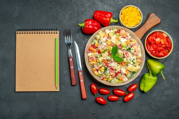 Top view of bowl of vegetable salad with cutleries veggies and notepad on side on dark grey table