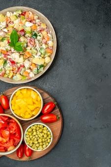 Vista dall'alto della ciotola di insalata di verdure con piatto di verdure sul lato e spazio libero per il testo su sfondo grigio scuro
