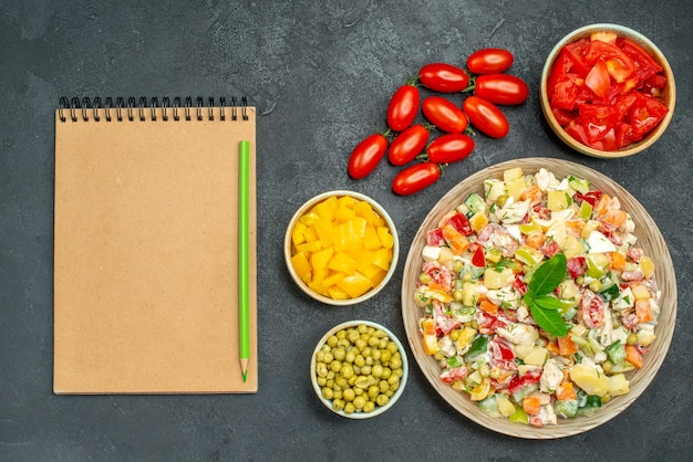 Top view of bowl of vegetable salad with vegetables and notepad on side on dark grey background