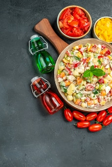 Top view of bowl of vegetable salad with vegetables and oil vinegar bottles on side with free space for your text on dark grey background
