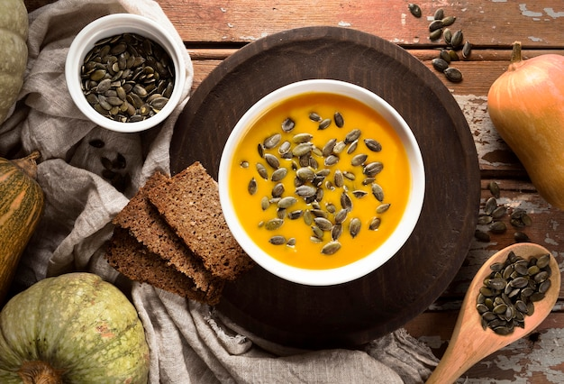 Top view of bowl with autumn squash soup and seeds