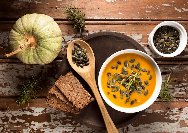 Top view of bowl with autumn squash soup with seeds and bread