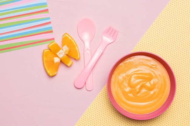 Top view of bowl with baby food and fruit with cutlery
