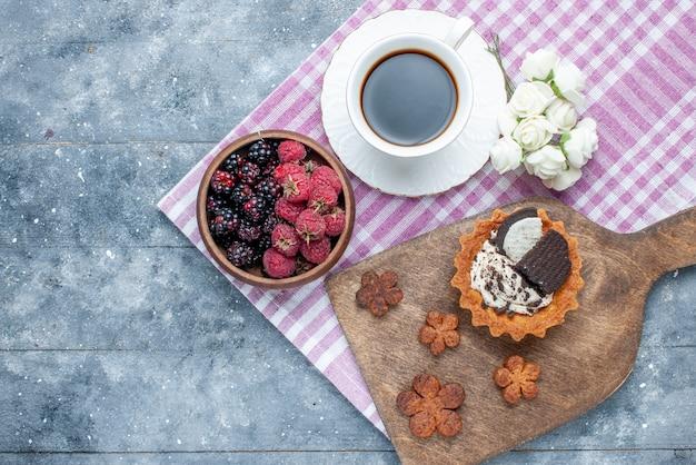 Vista dall'alto della ciotola con bacche frutta fresca e matura con biscotti al caffè su grigio, frutti di bosco freschi maturi mellow forest