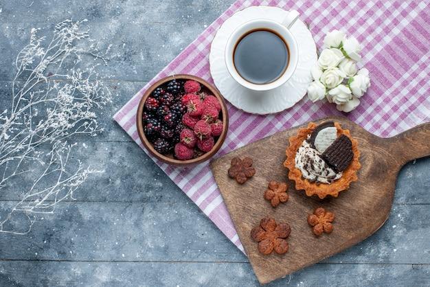 Vista dall'alto della ciotola con frutti di bosco frutta fresca e matura con biscotti al caffè sulla scrivania grigia, frutti di bosco freschi maturi mellow forest