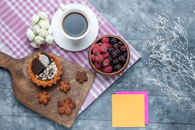 Vista dall'alto della ciotola con bacche frutta fresca e matura con biscotti e caffè sulla scrivania grigia, frutti di bosco freschi maturi mellow forest