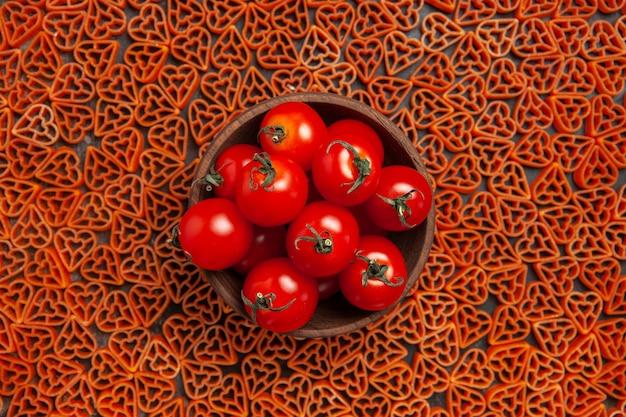 暗いテーブルの上の赤いハートのイタリアンパスタの周りにチェリートマトのトップビューボウル