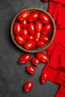 暗い背景にチェリートマトの赤いタオルとチェリートマトのトップビューボウル