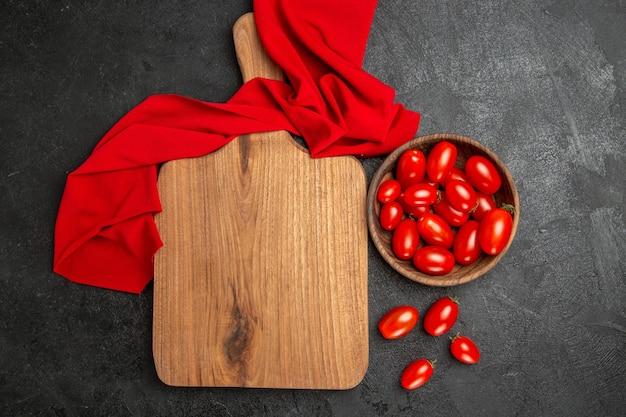 Vista dall'alto ciotola con pomodorini asciugamano rosso un tagliere e pomodorini su sfondo scuro