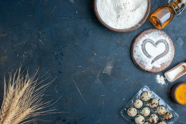 Vista dall'alto ciotola con farina di legno bordo curcuma in una piccola ciotola uova di quaglia sullo spazio libero del tavolo