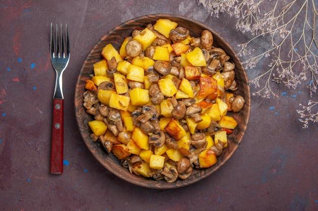 음식과 포크가 있는 탑 뷰 그릇과 감자와 버섯이 있는 접시가 테이블 위에 있습니다