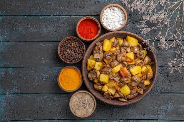 木の枝の隣にジャガイモとキノコとその周りのカラフルなスパイスが入った食べ物とスパイスのボウルが入った上面図ボウル