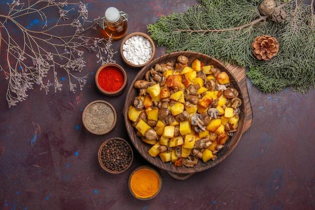 Ciotola vista dall'alto con ciotola per cibo con patate fritte e funghi diverse spezie e olio tra rami di alberi e coni