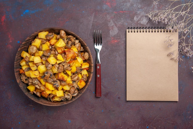 Top view bowl with food a bowl with potatoes with mushrooms fork and notebook