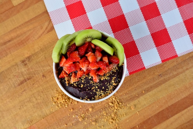 Top view of bowl with peanuts, kiwi fruit, strawberry and açai creamy on a plaid print napkin