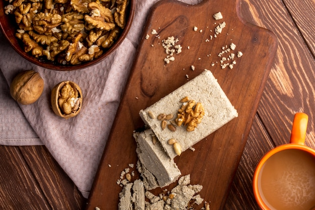 Top view of a bowl with walnuts and sweet halva slices on a wooden board