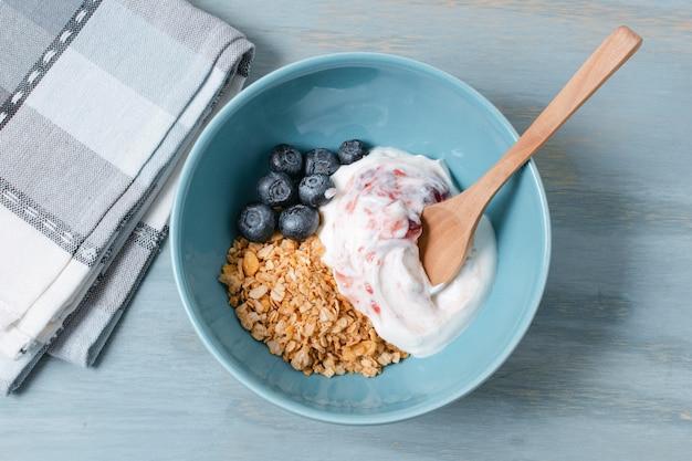 Вид сверху миску с йогуртом и овсом на столе