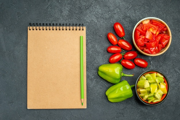 Top view of bowls of bell pepper and tomatoes with vegetables and notepad on side on dark green background