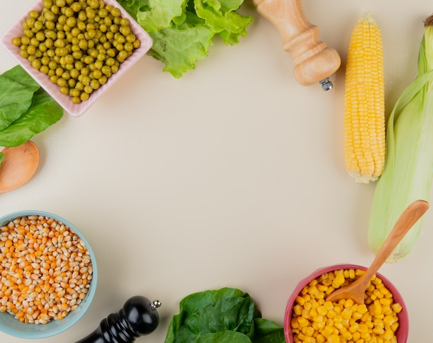 Top view of bowls of dried and cooked corn seeds green peas lettuce spinach corn cobs on white surface with copy space