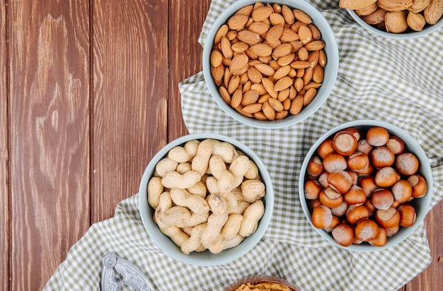 Top view of bowls filled with mixed nuts hazelnuts almond peanuts and walnuts on wooden background with copy space