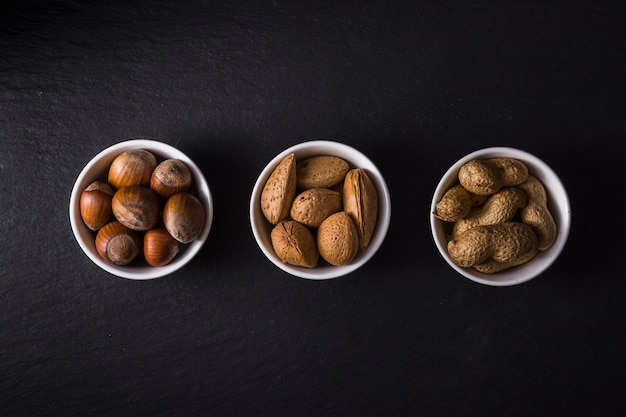 Top view bowls filled with tasty nuts