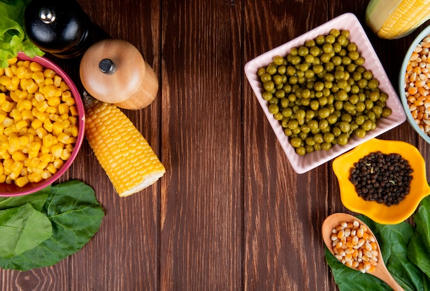 Top view of bowls of green peas corn seeds and black pepper with spinach on wooden surface