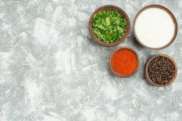 Vista dall'alto ciotole di spezie ciotole di spezie pepe nero erbe e panna acida sul lato destro del tavolo grigio