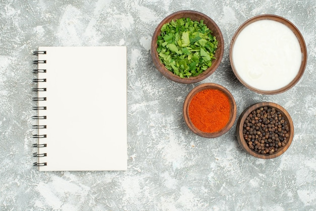 Top view bowls of spices bowls of spices black pepper herbs and sour cream next to white notebook on grey table