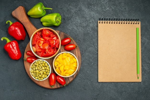 Top view of bowls of vegetables on plate stand with vegetables and notepadon side on dark grey background